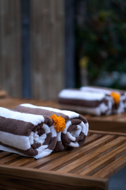 Rolled Up Towel Close Up On Sunbeds With Flowers