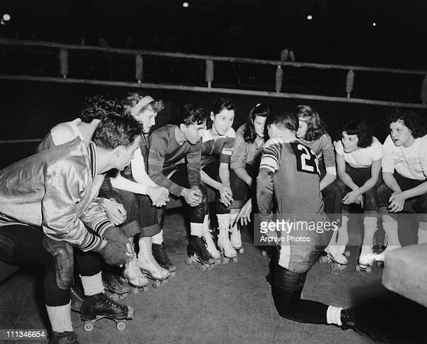 A roller derby team hold a team talk circa 1950