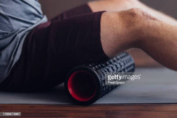 roller massage for warming up: an unrecognizable fit caucasian sportsman preparing to work out indoors - sportsperson stock pictures, royalty-free photos & images