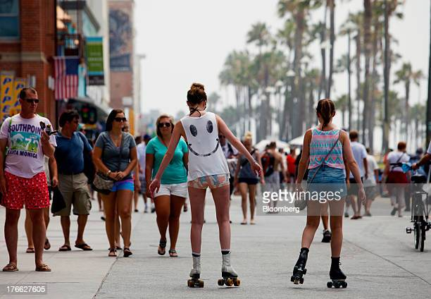 Roller skaters pass pedestrians on the strand at Venice Beach in Los Angeles California US on Wednesday Aug 14 2013 Overall US tourismrelated sales...