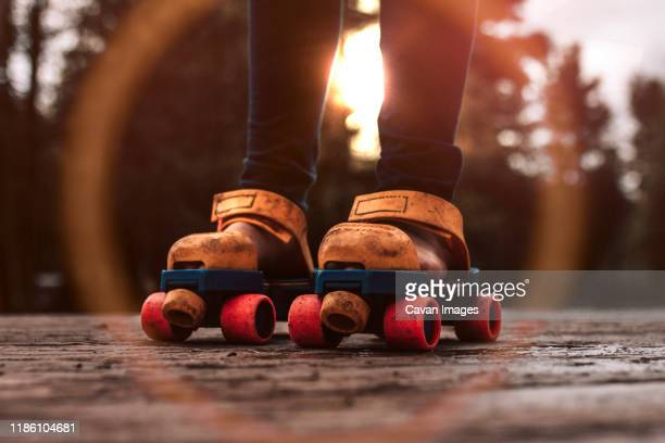 roller skating child playing outdoors with vintage toy roller skates - anno 1980 foto e immagini stock