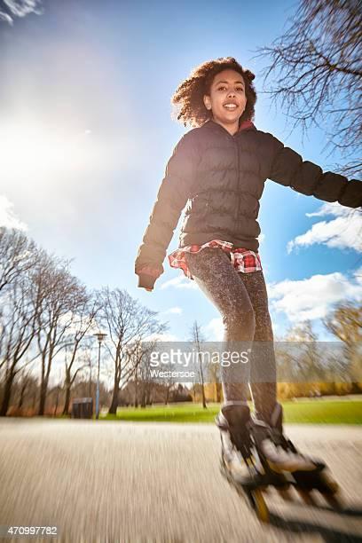 Roller skating tenage girl in motion, backlit urban scene outdoor