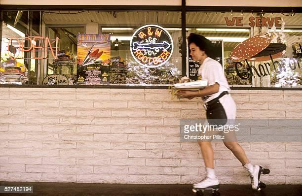 A roller skating waitress delivers an order at a drivethru restaurant in Modesto California USA