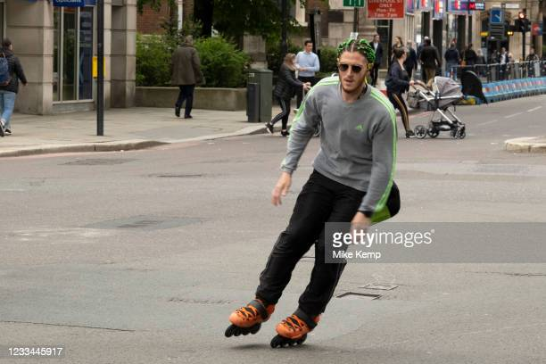 Rollerblading in the City of London on 26th May 2021 in London, United Kingdom. Man with green hair, rollerblades along Bishopsgate taking advantage...