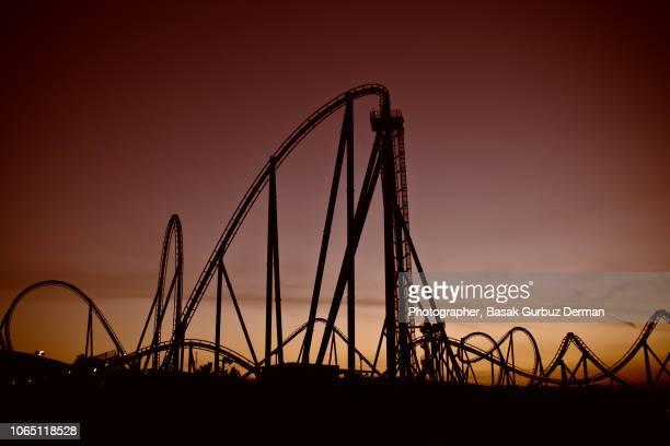 rollercoaster at sunset - basak gurbuz derman stock photos and pictures