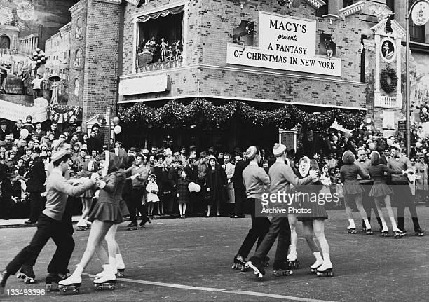 Rollerskating teens during the Macy's Day Parade at Thanksgiving in New York City 26th November 1961 The sign behind reads 'Macy's Presents a Fantasy...