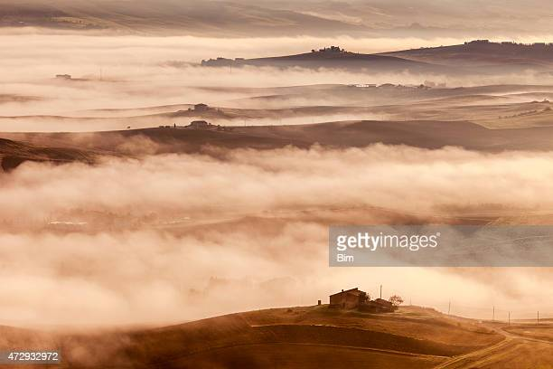 rolling hills, farmhouses and morning fog in tuscany, italy - bronze colored stock pictures, royalty-free photos & images