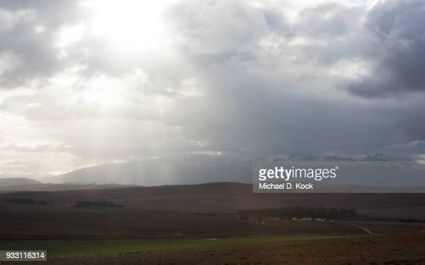 rolling hills of the cape overberg, farmland, with snow capped mountains in the distance, sunlight playing a dance, western cape - overberg stock pictures, royalty-free photos & images