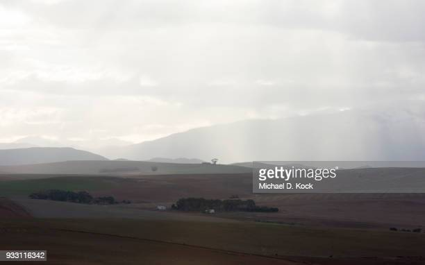 rolling hills of the cape overberg, farmland, with snow capped mountains in the distance, rain showers and sunlight playing a dance, western cape - overberg stock pictures, royalty-free photos & images
