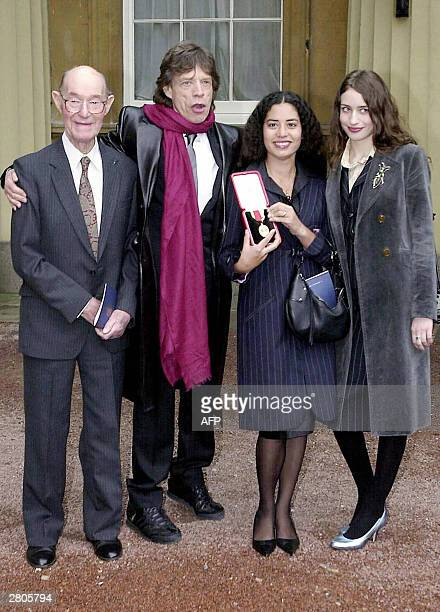 Rolling Stone Sir Mick Jagger stands with his 92yearold father Joe and daughters Elizabeth 19 and Karis who holds aloft the knighthood he received...