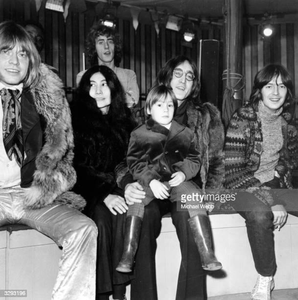 Rolling Stones guitarist Brian Jones artist Yoko Ono and her husband Beatles guitarist John Lennon with his son Julian on his lap guitarist Eric...