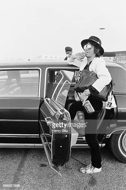 Rolling Stones guitarist Keith Richards exits his limousine at an airport