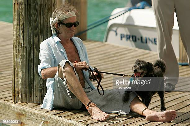 Rolling Stones guitarist Keith Richards lounges with his dog on a dock at Parrot Cay a 1000–acre private island resort in the Turks and Caicos...