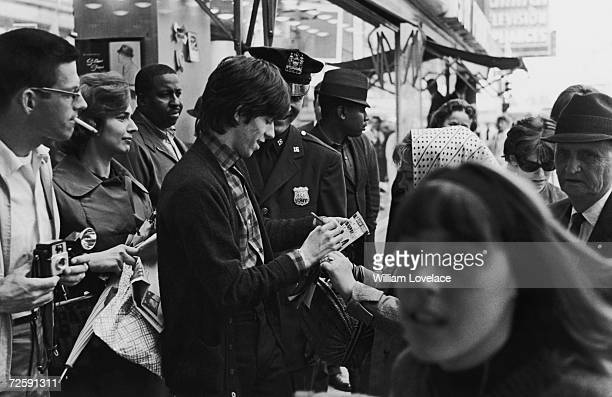 Rolling Stones guitarist Keith Richards signs autographs for fans in new York, June 1964.