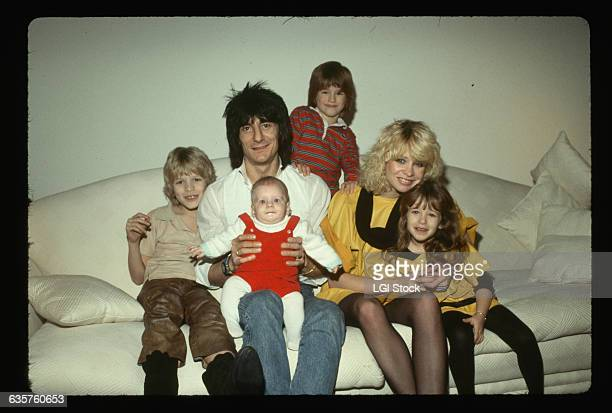 Rolling Stones guitarist Ron Wood sits on a couch with his girlfriend Jo Howard and children.