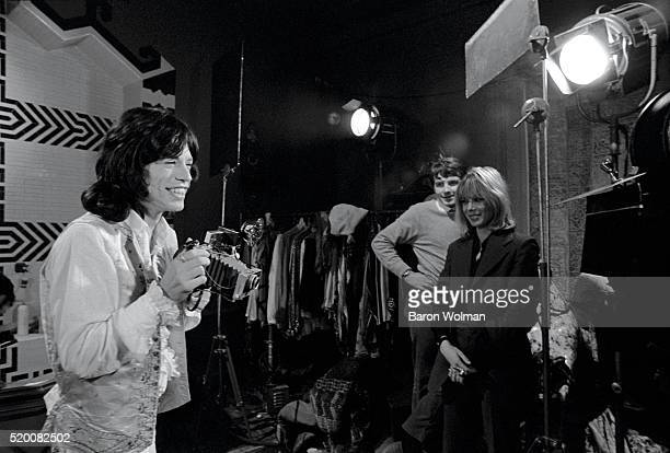 Rolling Stones' Mick Jagger takes a photograph on the set of 'Performance' with Anita Pallenberg in the background Shepperton Studios London...