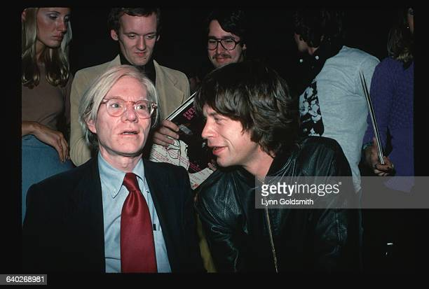 Rolling Stones singer Mick Jagger talks to artist Andy Warhol as fans stand and watch