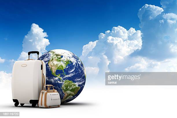 Rolling suitcase, bag and Earth with beautiful sky on background