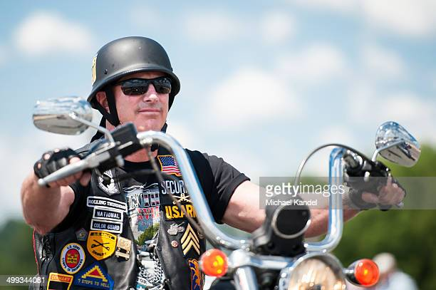 Rolling Thunder participant covered in military patches rides by the Lincoln Memorial