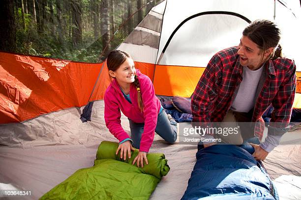 Rolling up sleeping bags in a tent.
