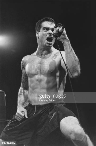 LOS ANGELES Rollins Band at Universal Amphitheatre November 24 Black and white view of Henry Rollins singing into upheld microphone while performing...