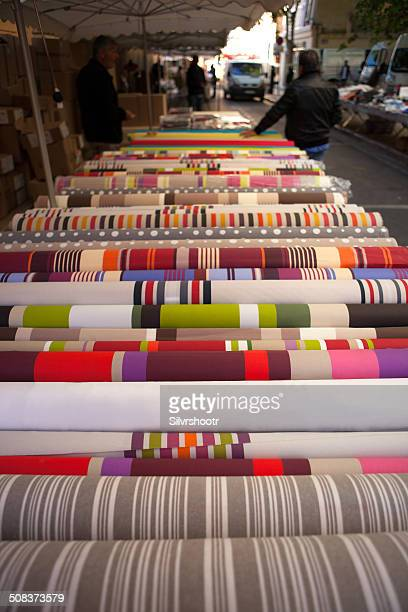 Rolls of fabric at a market.