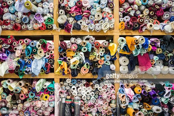 Rolls of fabric in a wooden shelf