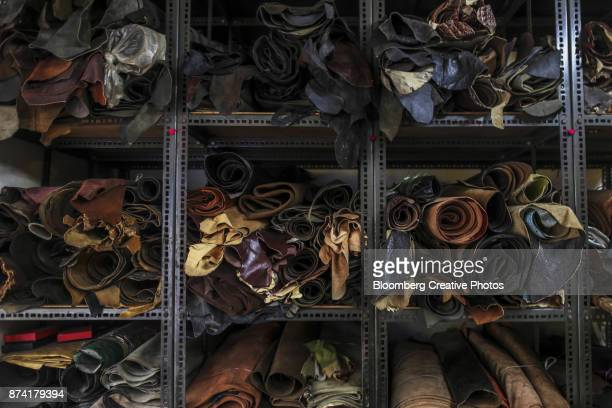 Rolls of leather sit stacked at a leather store