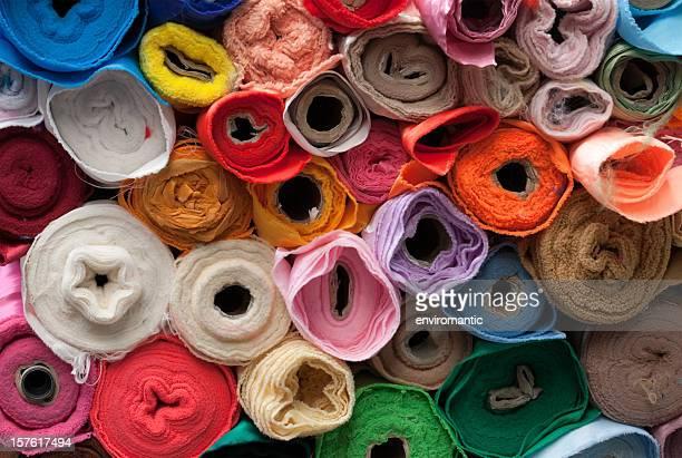 Rolls of multicoloured textiles.