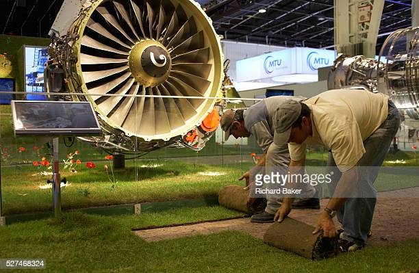 Rolls of turf are rolled up by exhibition workers at the end of a long day at the Paris Air Show, Le Bourget France. Removing the real grass from at...