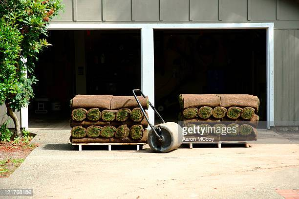 rolls of turf on wooden pallets and roller in front of garage, usa - turf stock pictures, royalty-free photos & images