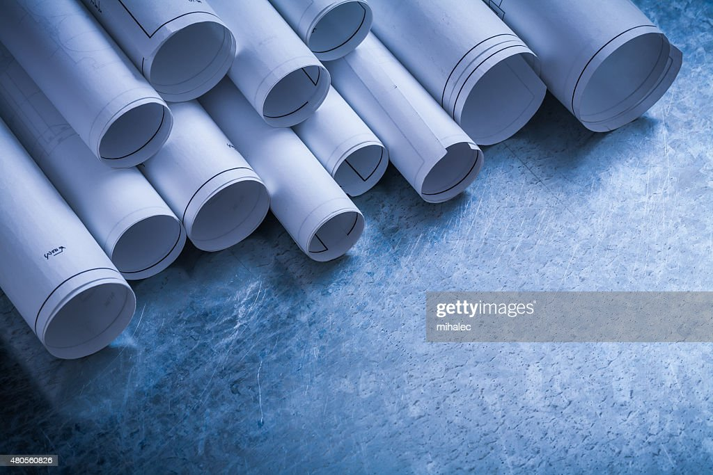 Rolls of white construction drawings on scratched metallic backg : Stock Photo