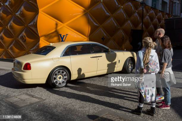 A RollsRoyce limousine drives past less wealthy onlookers opposite the temporary renovation hoarding of luxury brand Louis Vuitton in New Bond Street...
