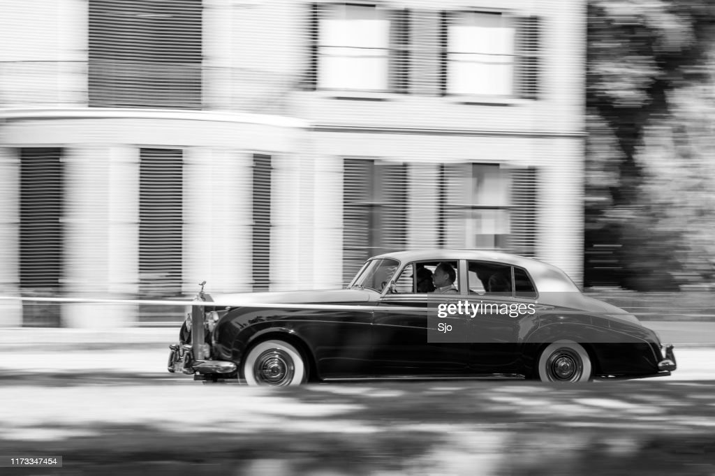 Rolls-Royce Silver Cloud driving at high speed on a road through a forest : Stock Photo