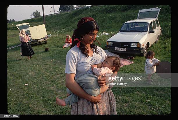 A Rom woman nurses her baby near a group of Rom women and their children congregating on the side of a highway in Romania