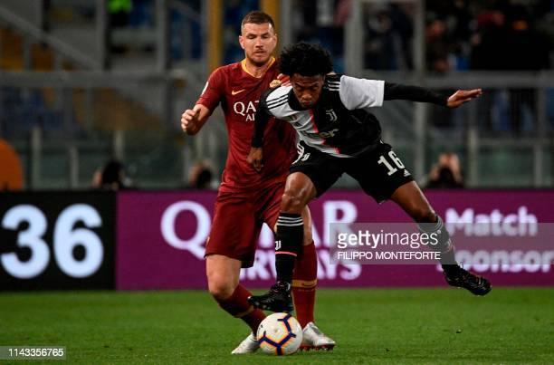 AS Roma Bosnian forward Edin Dzeko fights for the ball with Juventus' Colombian midfielder Juan Cuadrado during the Italian Serie A football match...