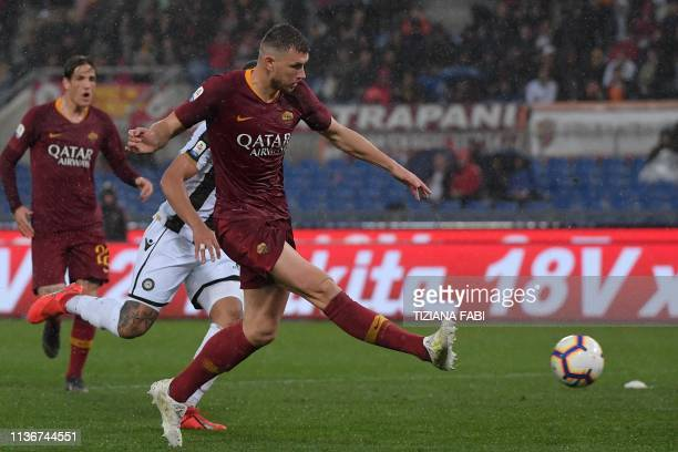 AS Roma Bosnian forward Edin Dzeko shoots to open the scoring during the Italian Serie A football match AS Roma vs Udinese on April 13 2019 at the...
