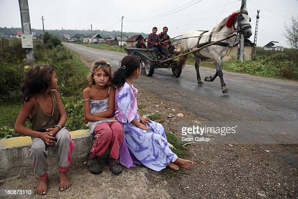 Roma children Marina AndreaMaria and Valeria sit on a curb as other Roma ride by on a horsedrawn cart which is the main means of trnaportaiton for...