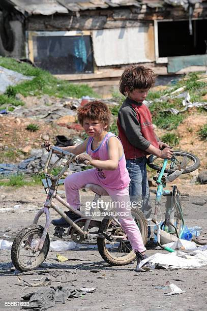 Roma children play with bicycles on the edge of a Roma settlement in the Sarajevo suburb of Butmir on April 8 2009 a day declared International Roma...