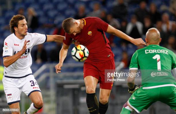 Roma Edin Dzeko left is challenged by Crotone Stefan Simic left and goalkeeper Alex Cordaz during the Serie A soccer match between Roma and Crotone...