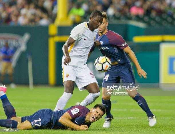 Roma forward Umar Sadiq center tries to control the ball tugging on the shirt of Paris SaintGermain midfielder Lorenzo Callegari right and stepping...