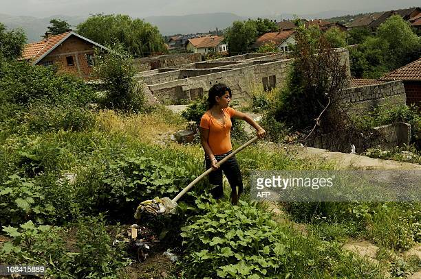 Roma girl works in front of her house in the town of Pec on June 19, 2010. For Roma kids expelled by Germany, Kosovo is a nightmare. They arrived in...
