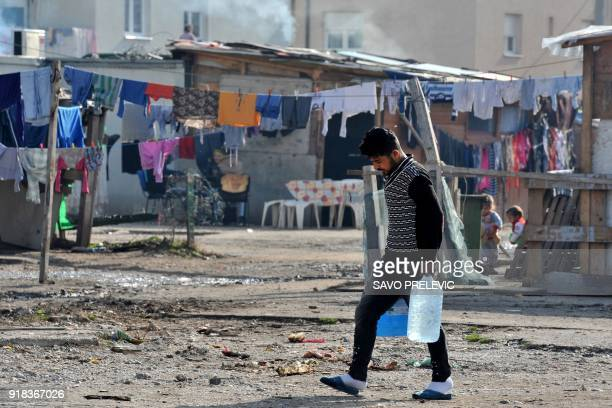 A Roma man carries water in a camp in the suburb of Konik in Podgorica on February 6 2018 It was not their war but the 1990s Kosovo conflict forced...