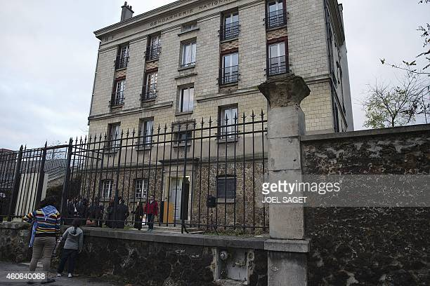 Roma people stand in front of a former gendarmerie that has been renovated to host 11 Roma families on December 18 2014 in IvrysurSeine southern...