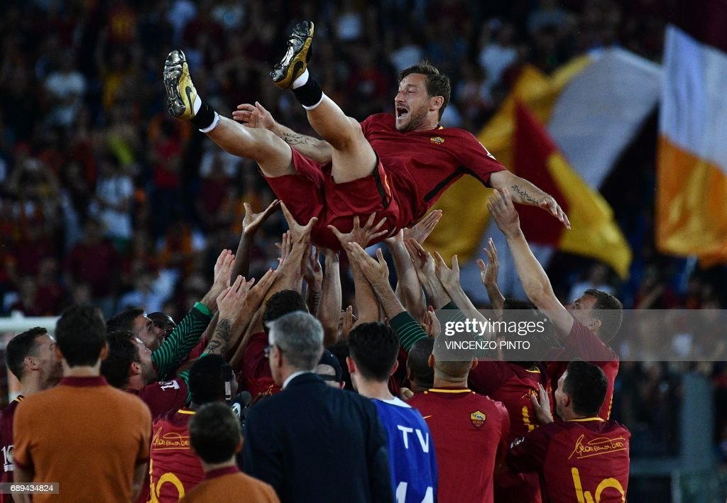 Roma players celebrate Roma's captain Francesco Totti during a ceremony following his last match with AS Roma after the Italian Serie A football match AS Roma vs Genoa on May 28, 2017 at the Olympic Stadium in Rome. Italian football icon Francesco Totti retired from Serie A after 25 seasons with Roma, in the process joining a select group of 'one-club' players. / AFP PHOTO / Vincenzo PINTO