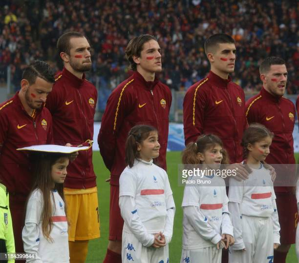 Roma playerss pose with the red mark on the face to support the campaign 'un rosso alla violenza' during the Serie A match between AS Roma and...