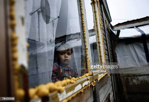 Roma refugee looks through a window in his house in the Cesmin Lug refugee camp in the Serbian district December 12 2007 in Kosovo province Serbia...