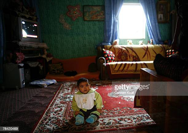 Roma refugee sits on the floor in the living room of her family home in the Cesmin Lug refugee camp in the Serbian district December 12 2007 in...