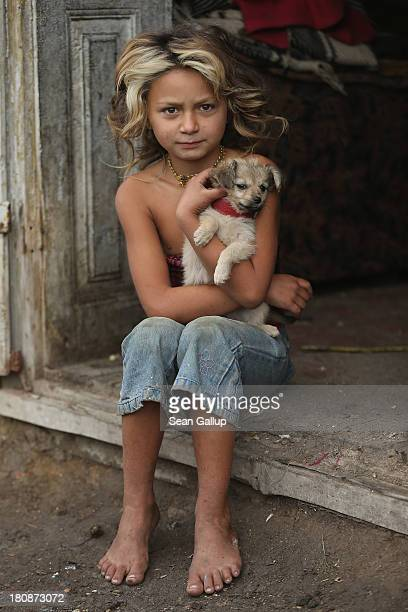 Roma resident Denisa Varga clutches her puppy Anka while sitting on the doorstep of the tworoom hut she shares with her parents siblings and...