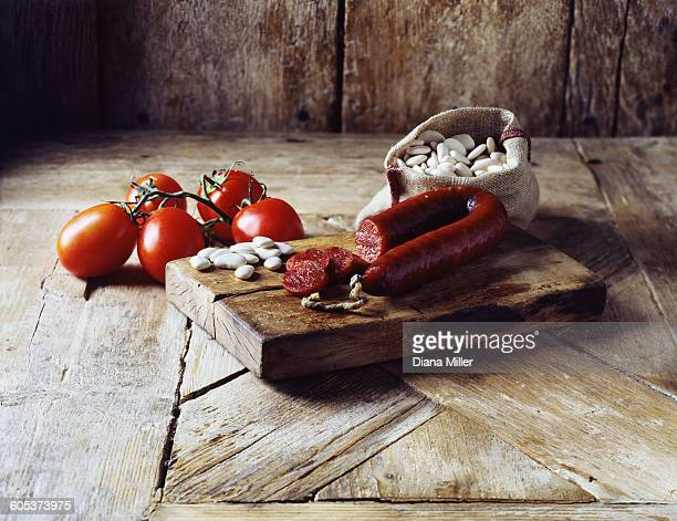 Roma tomatoes on the vine, chorizo and butter beans in burlap sack on wooden cutting board